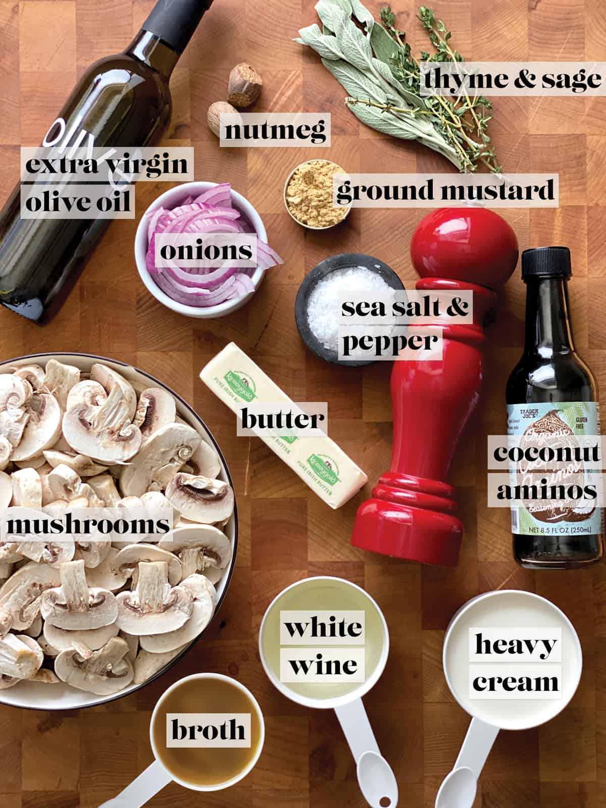 Ingredients for mushroom sauce.  A bowl of mushrooms, a stick of butter, a bottle of extra virgin olive oil, a cup with white wine, a cup of heavy cream, a small cup with ground mustard and nutmeg, a bottle of coconut aminos, fresh herbs like thyme leaves, some sea salt and freshly ground pepper on a butcher block.