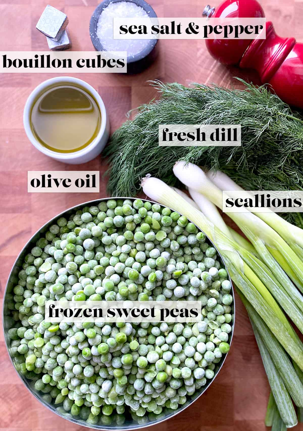 On aa butcher block, two bouillon cubes, a small bowl with sea salt, a red pepper mill, a small container with olive oil, a bunch of fresh dill, five fresh scallions and a large bowl with frozen peas.