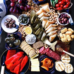 A cutting board with grapes, pita bread, a bowl with anchovies, confiners with fig jam and artichoke spread, a fish sjhaped bowl with biscotti. Scattered walnuts and pistachios, sliced figs and mini triangle cheese pies and cubes of feta cheese.