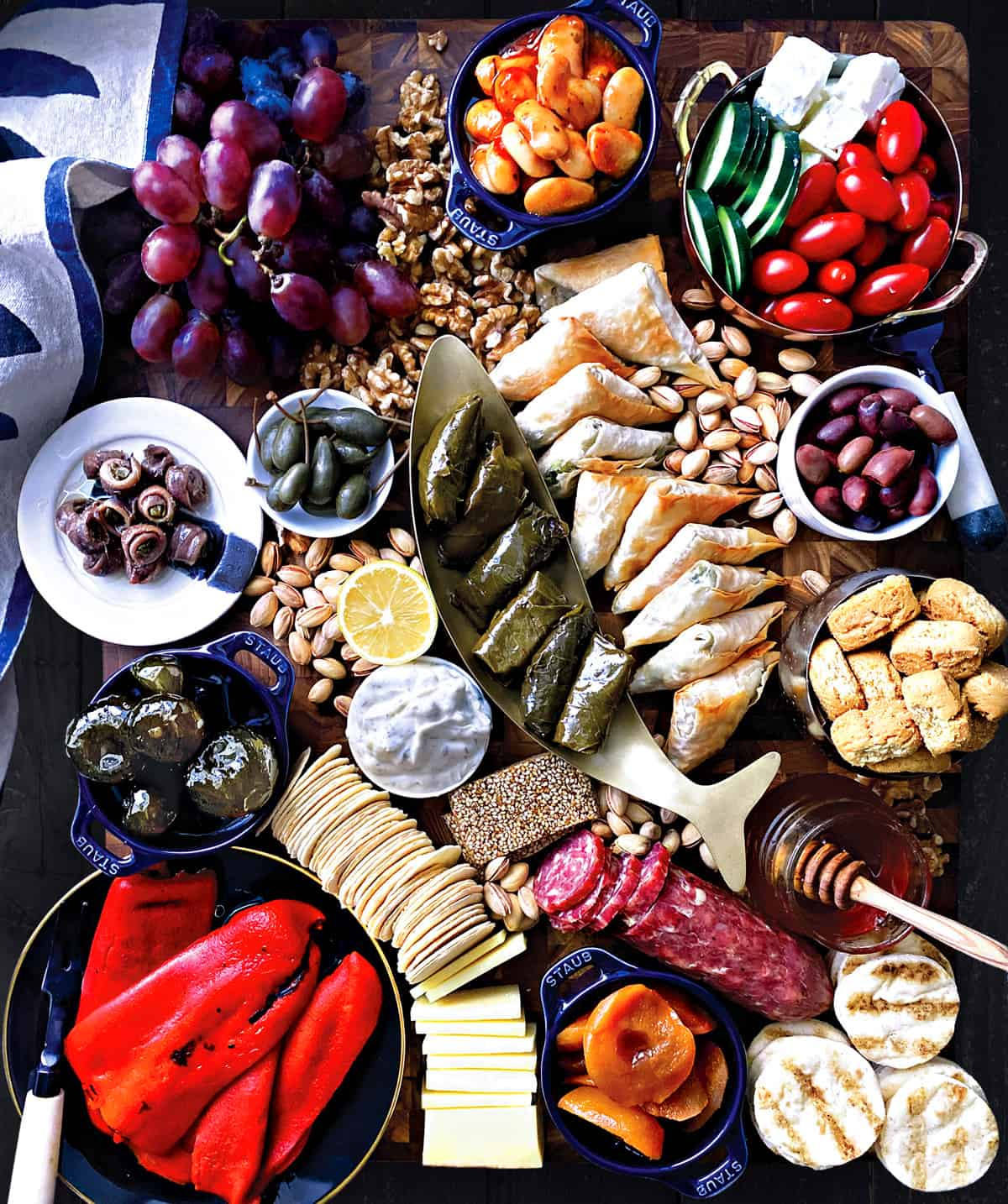 A cutting board with grapes, pita bread, a bowl with anchovies, confiners with fig jam and artichoke spread, a fish shaped bowl with biscotti. Scattered walnuts and pistachios, sliced figs and mini triangle cheese pies and cubes of feta cheese. Bowl with greek salad, a plate with red peppers and a salami, sliced.