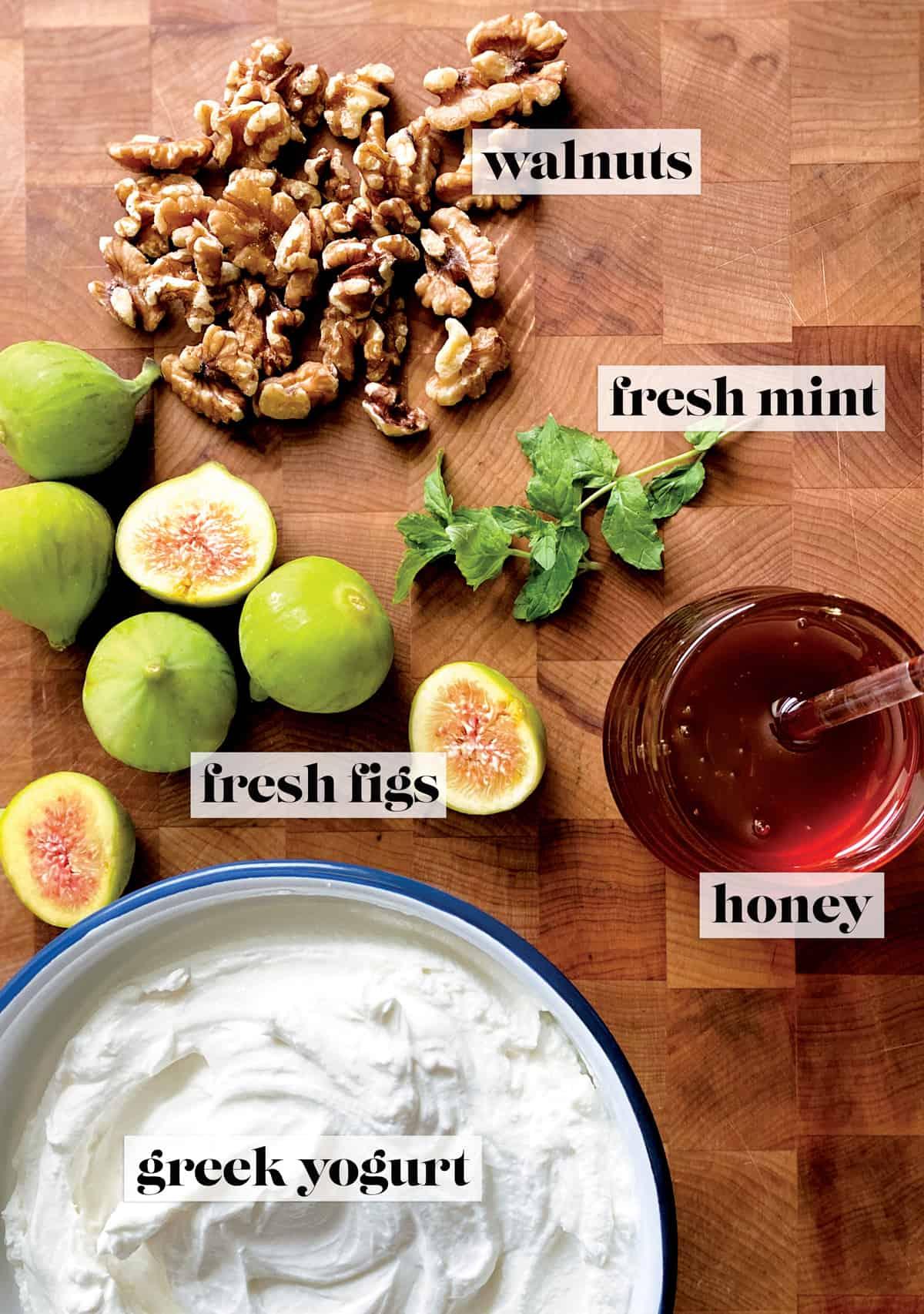 Fresh figs, walnuts, two fresh mint twigs, a pot of honey and a bowl of yogurt on a butcher block.