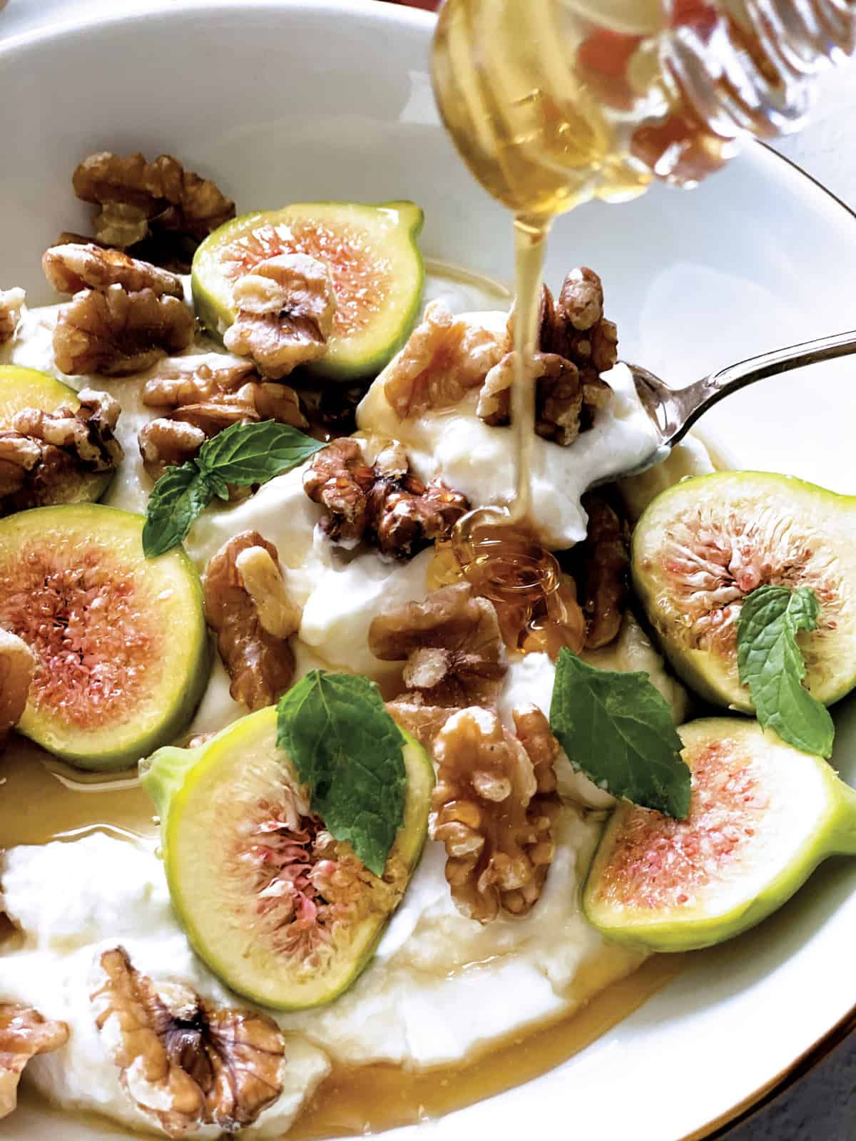 Close up of yogurt, figs and walnuts and a honey dipper drizzling honey.