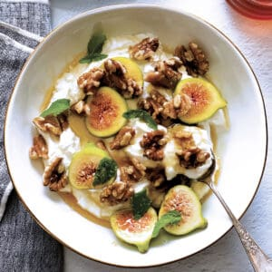 A plate with yogurt, sliced figs, walnuts and honey and a spoon. At the back a plate with figs and nuts.