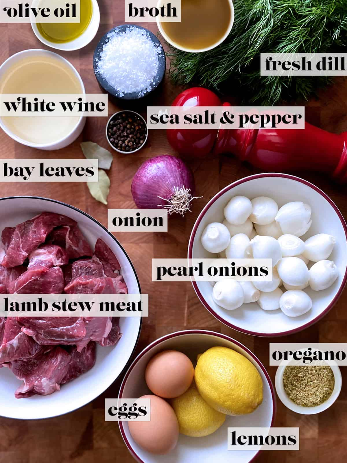 Ingredients for lamb stew. Small bowls with salt, olive oil, broth, pepper, white wine. A bunch of fresh dill, a pepper grinder, two bay leaves, an onion, a bowl with lamb stew cubes, a bowl with pears onions, a bowl with two eggs and two lemons and a small bowl with oregano, all on a butcher block.