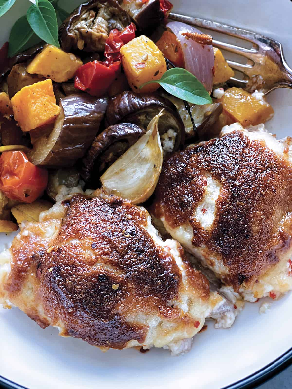 Two pieces of parmesan crusted chicken with mayo and vegetables on a plate, and a fork.