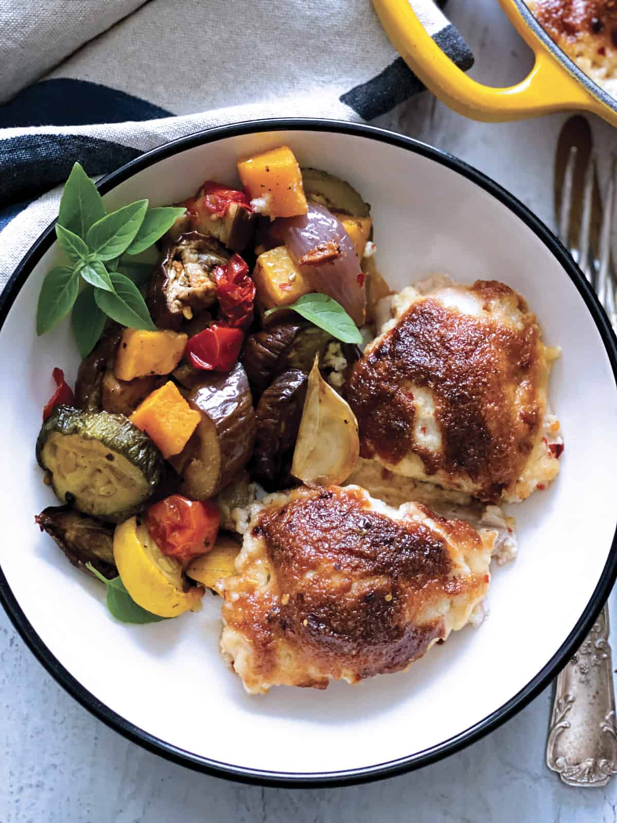 Two pieces of parmesan crusted chicken with mayo and vegetables on a plate, part of a yellow pan with chicken at the back and a cloth napkin, all on a white table.