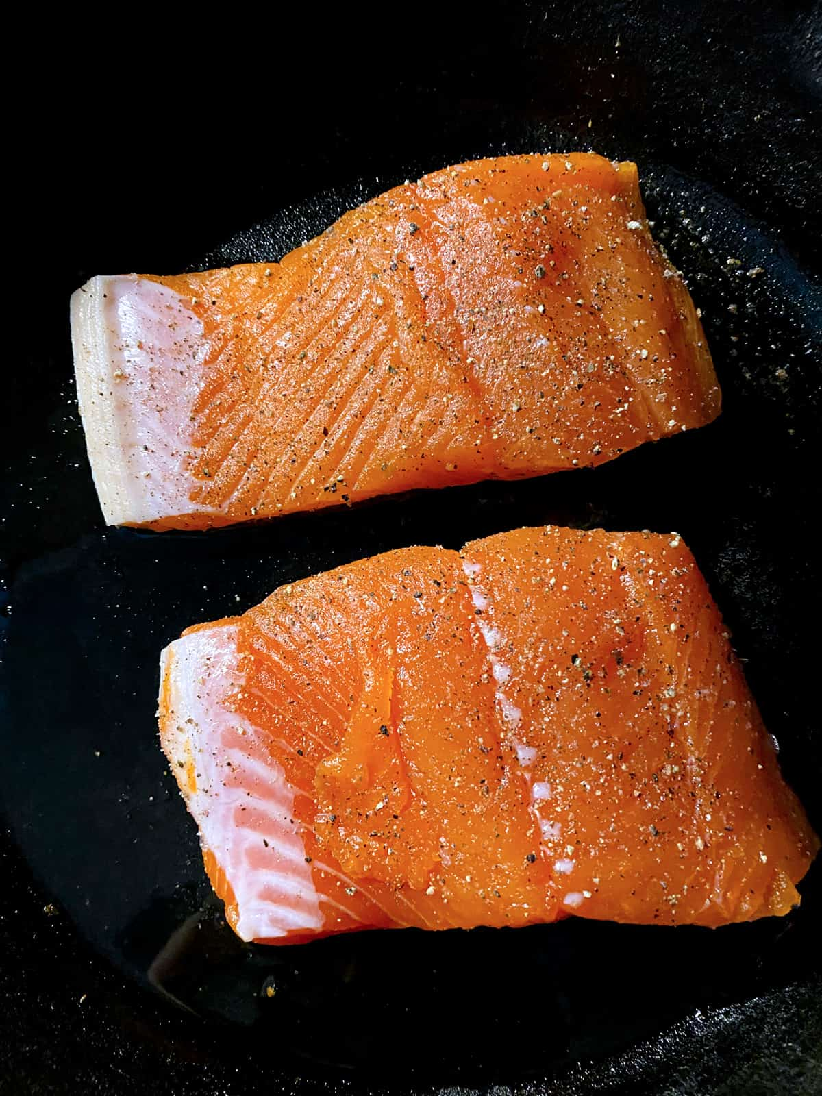 Two pieces of salmon cooking.