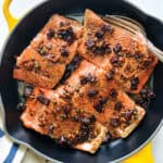 Brown butter salmon with capers and sundried tomatoes in a yellow pan with a cloth napkin on a white table.