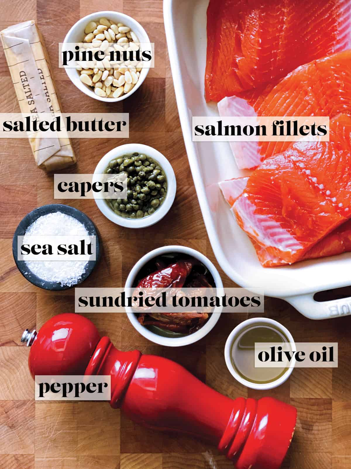 A baking pan with fresh salmon fillets, a pepper mill, a bowl with sundried tomatoes, a bowl with pine nuts, a bowl with capers a bowl with olive oil and a bowl with salt and a stick of butter.
