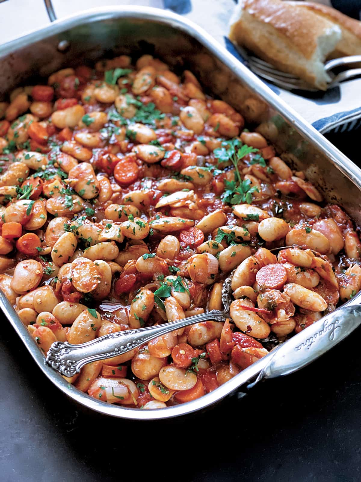 A baking pan with gigantes beans, carrots, fresh parsley and a spoon. A napkin with serving utensils and pieces of bread on the side.