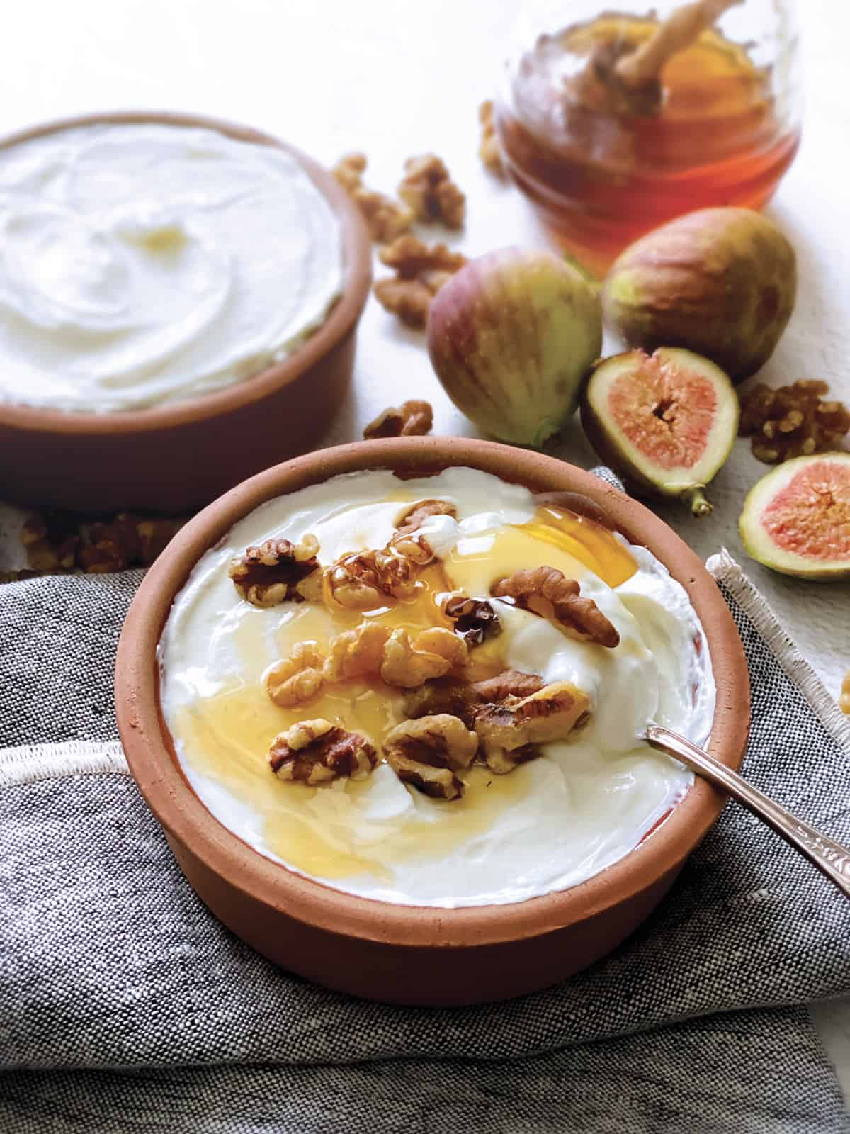 A bowl with yogurt, honey and walnuts, a spoon on a cloth napkin, fig halves, another bowl with yogurt and a jar with honey.