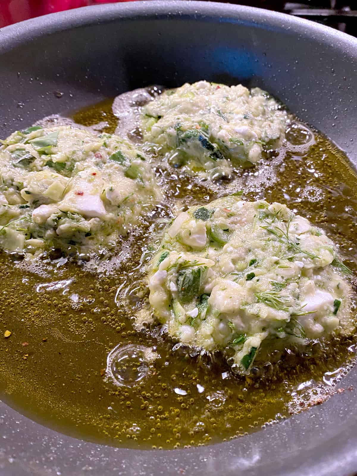 Three fritters frying in olive oil.