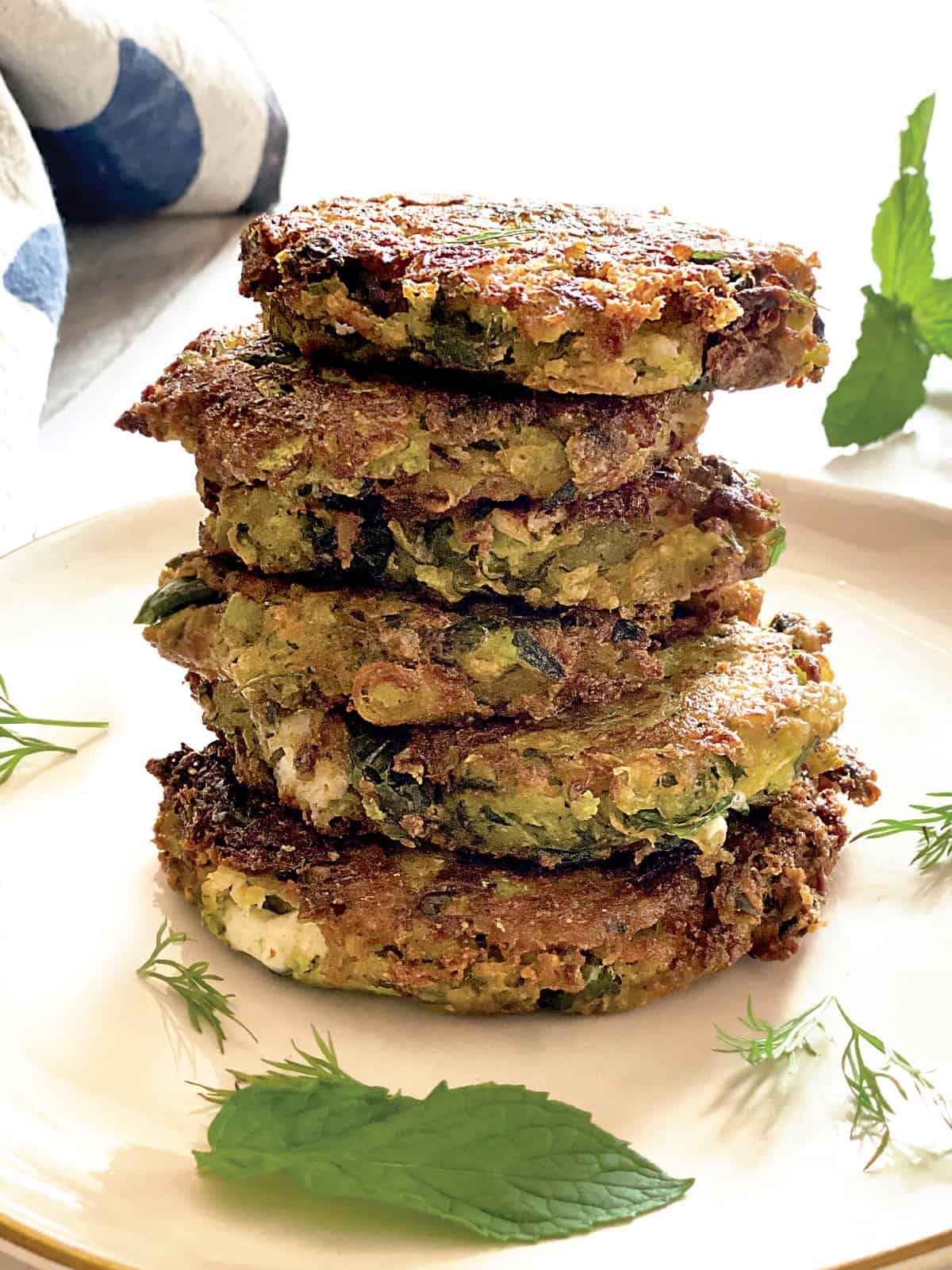 A plate with stacked fritters, at the back a napkin and some herbs.