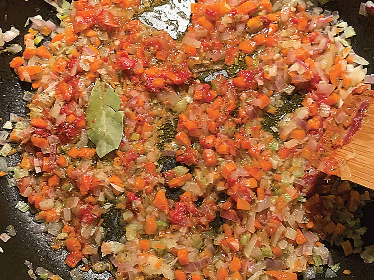 Diced onion and carrots with tomato paste and a bay leaf in olive oil and a spatula.