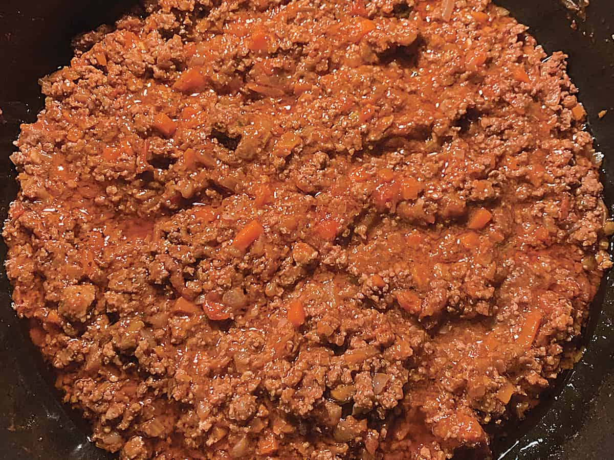 Greek bolognese sauce with diced carrots in a pot.