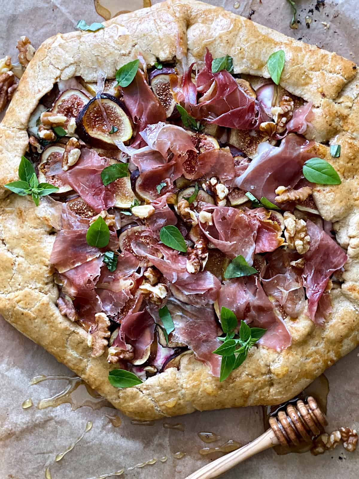 A savory galette with figs and prosciutto and a honey dipper on parchment paper.