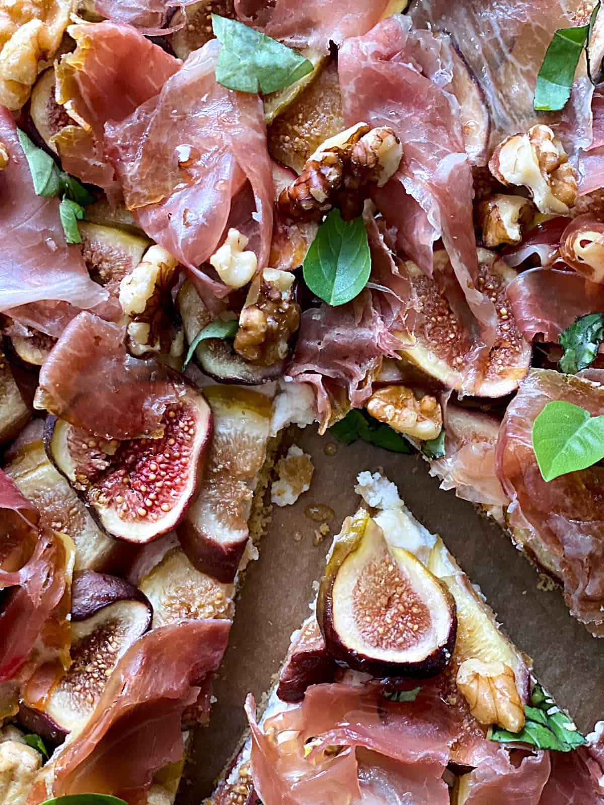 A savory galette with figs and prosciutto, a piece cut out on parchment paper.