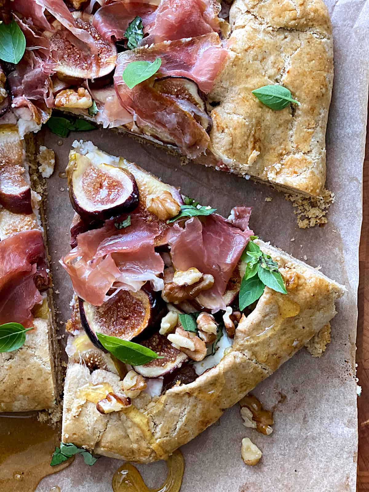 A savory galette with figs and prosciutto, a piece cut out and a honey dipper on parchment paper.