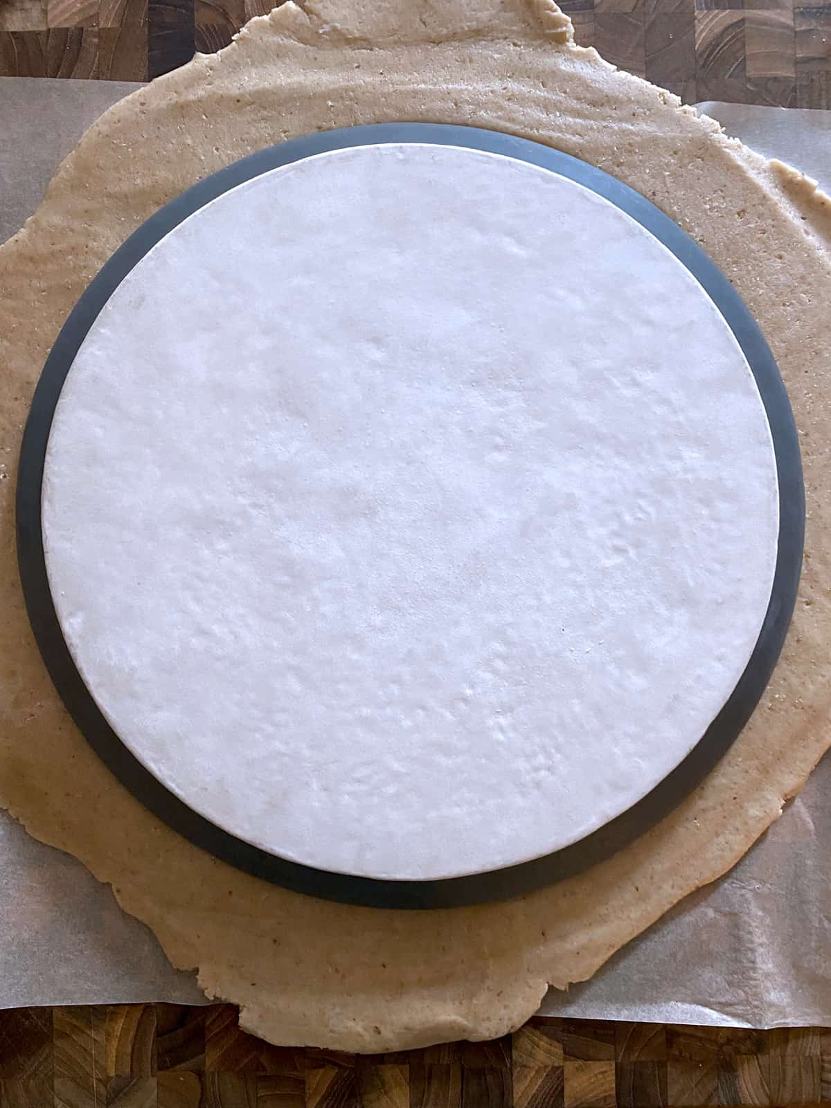 A plate on pie dough on a working surface.