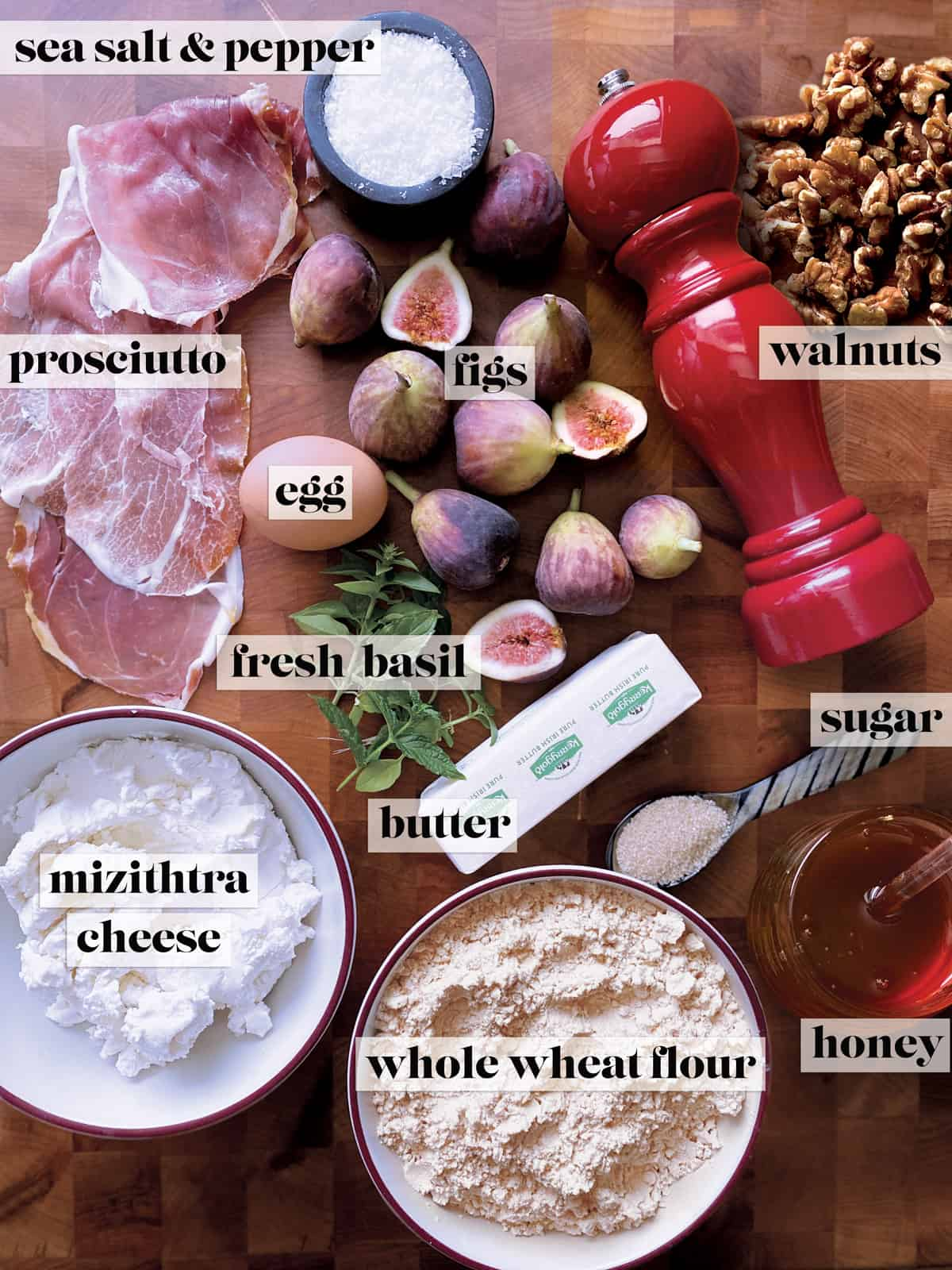 Slices of prosciutto, an egg, figs, a container with salt, a pepper mill, some walnuts, fresh basil, a spoon with sugar, a stick of butter, a bowl with cheese, a bowl with flour and a pot of honey.