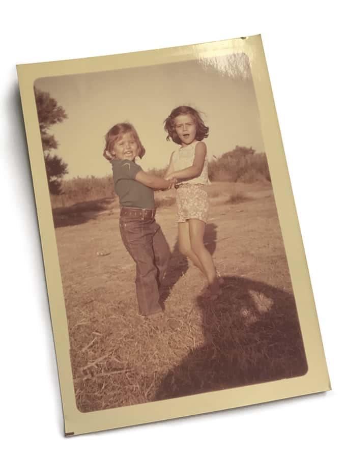 Two girls swirling in a field.
