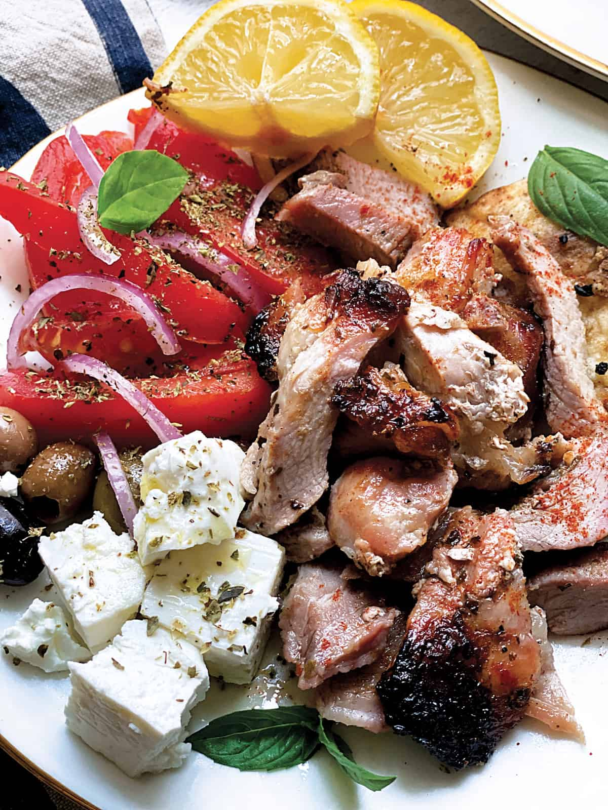 A plate with sliced tomatoes and onions, olives, feta cheese cubes, pieces of gyro, lemon wedges and pitas.