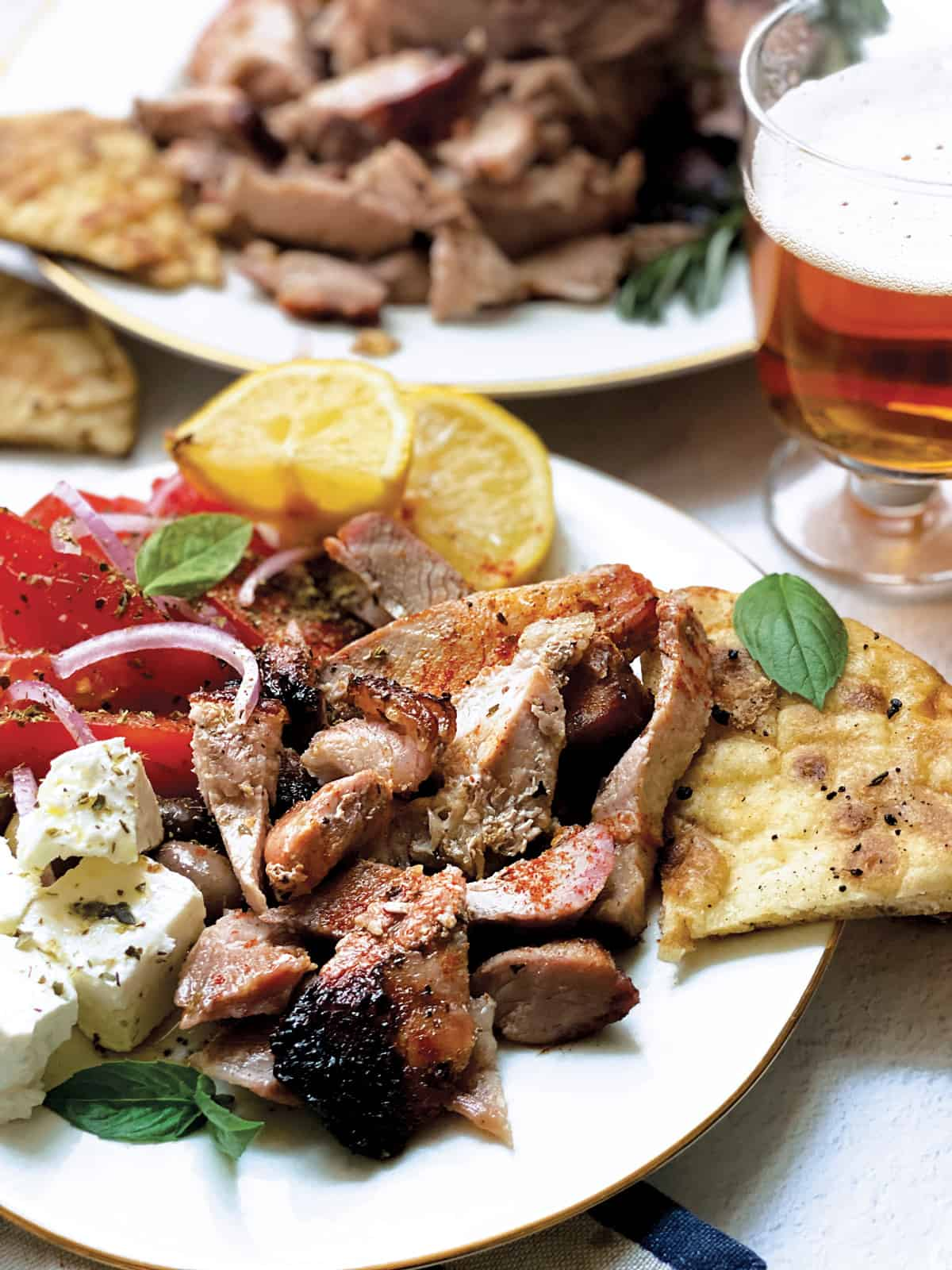 A plate with sliced tomatoes and onions, olives, feta cheese cubes, pieces of greek gyro lemon wedges and pitas.