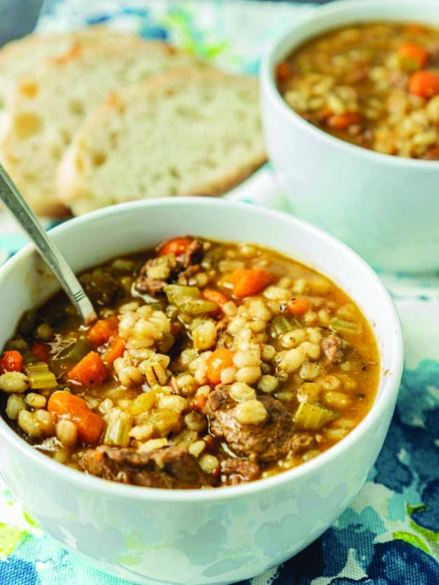 A bowl with beef and barley soup and a spoon.