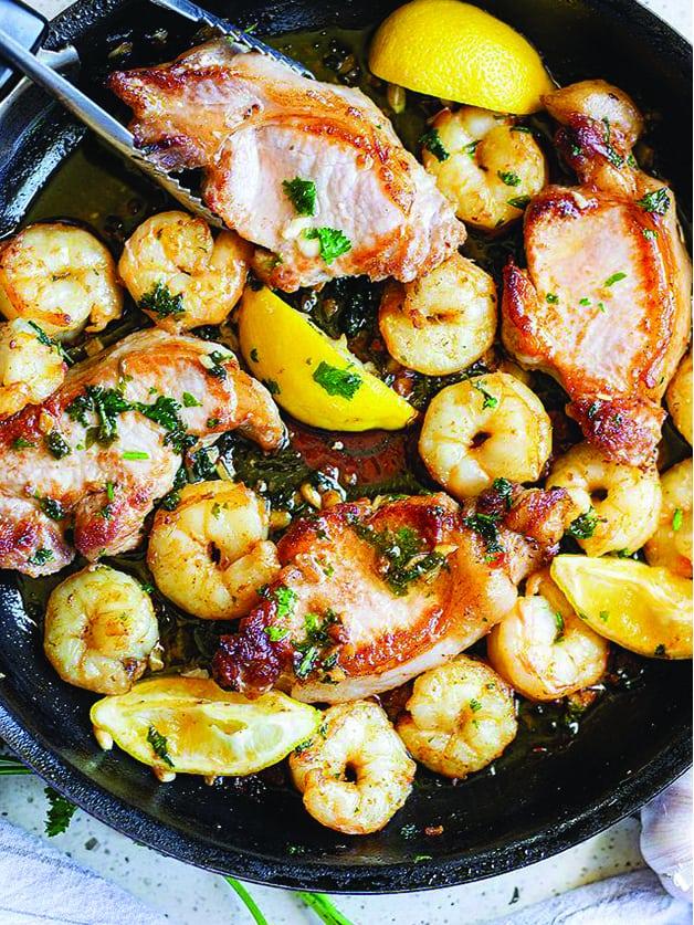 A skillet with pork chops , lemon wedges and shrimp.