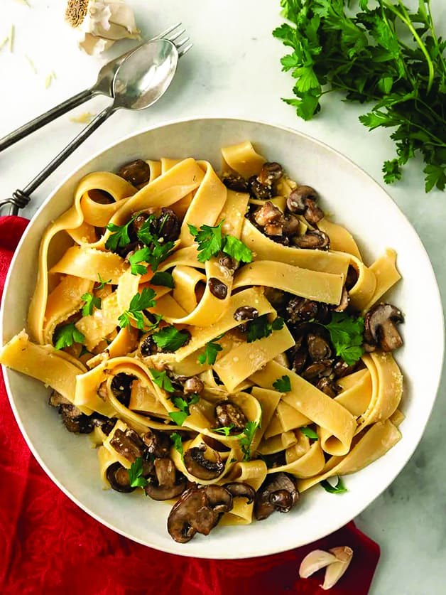 A plate with papardele pasta with mushrooms.