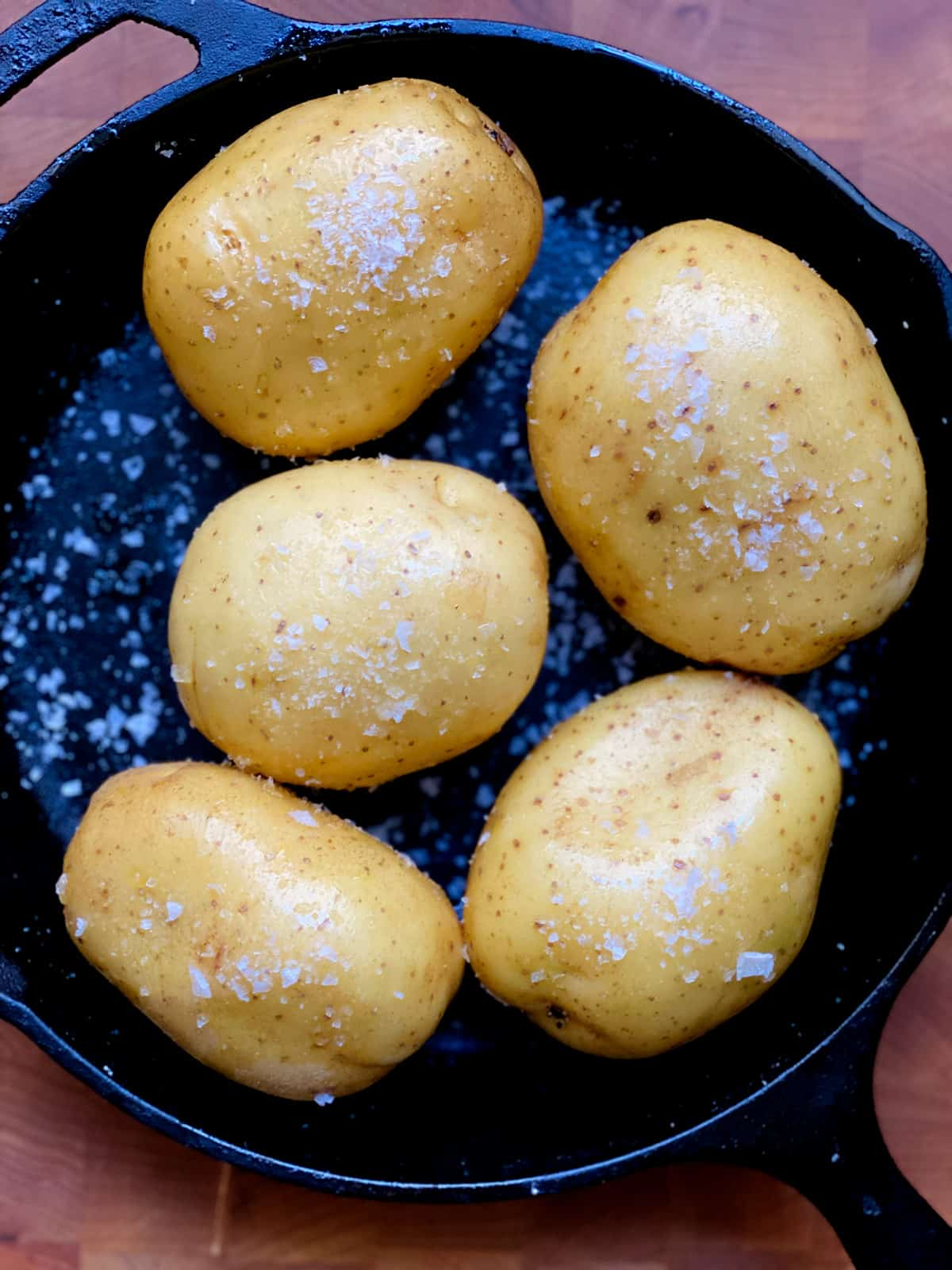 Five potatoes with salt in a cast iron.