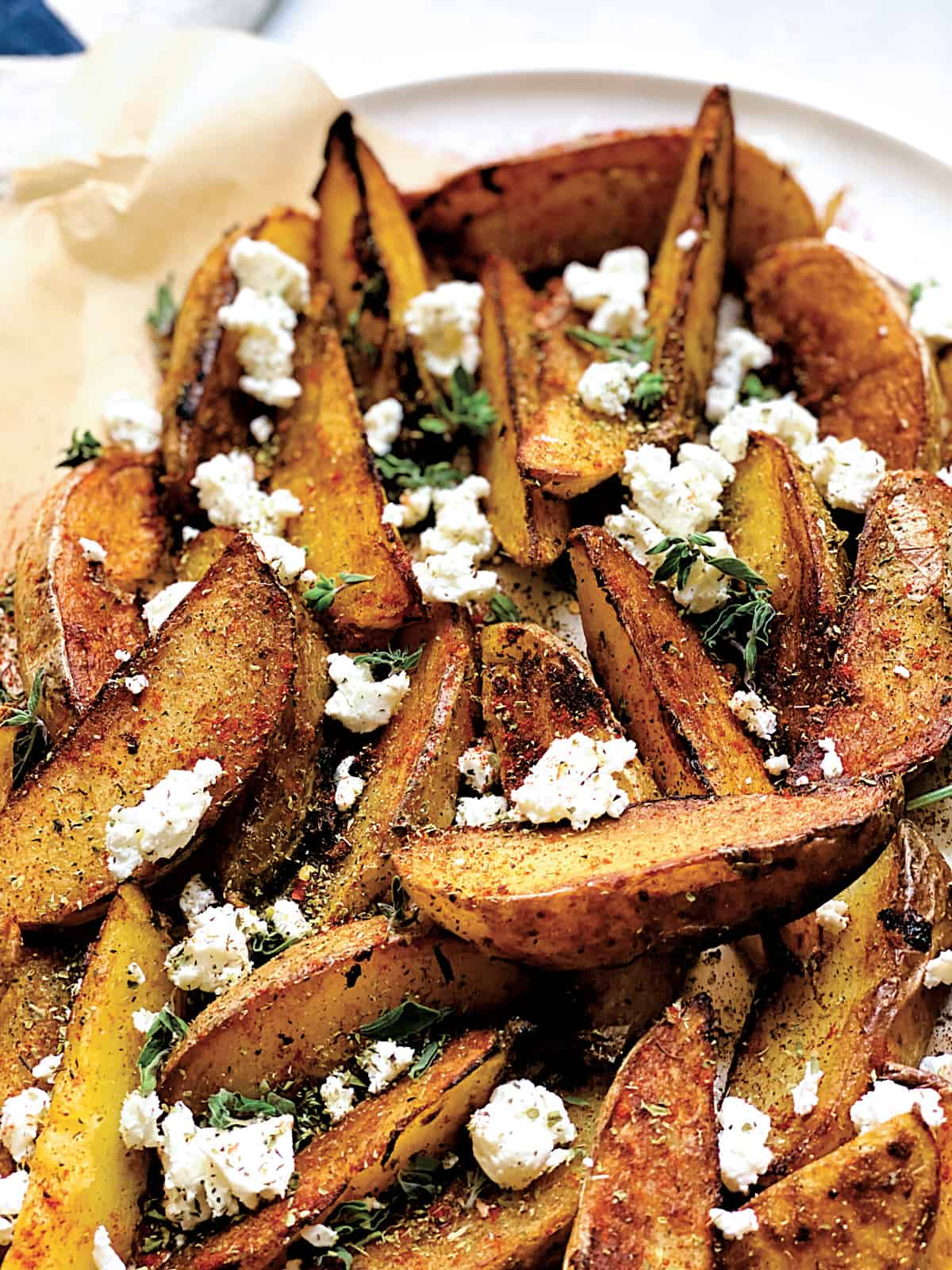 A platter with greek fries on a parchment paper with crumbled feta and herbs and seasonings.