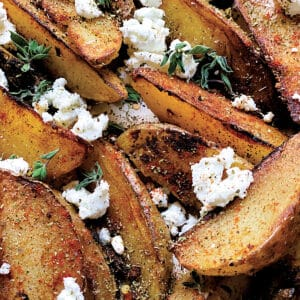Close up of greek fries with feta and herbs.