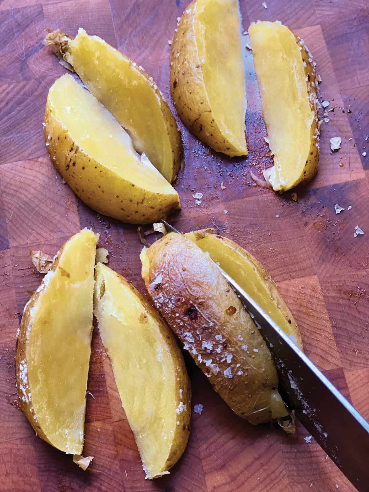 A hand cutting potatoes in wedges.