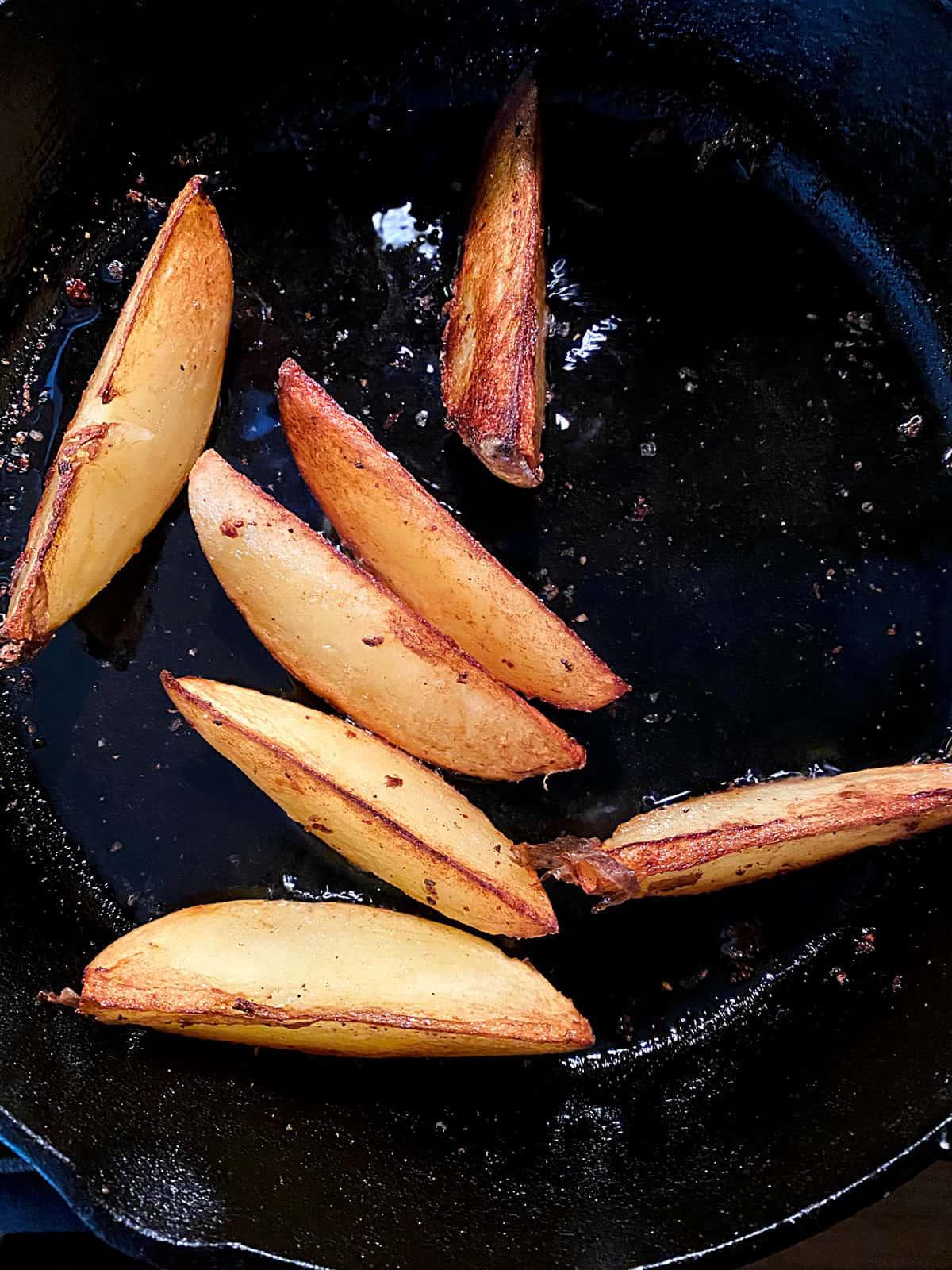 Potato slices frying in a cast iron pan.