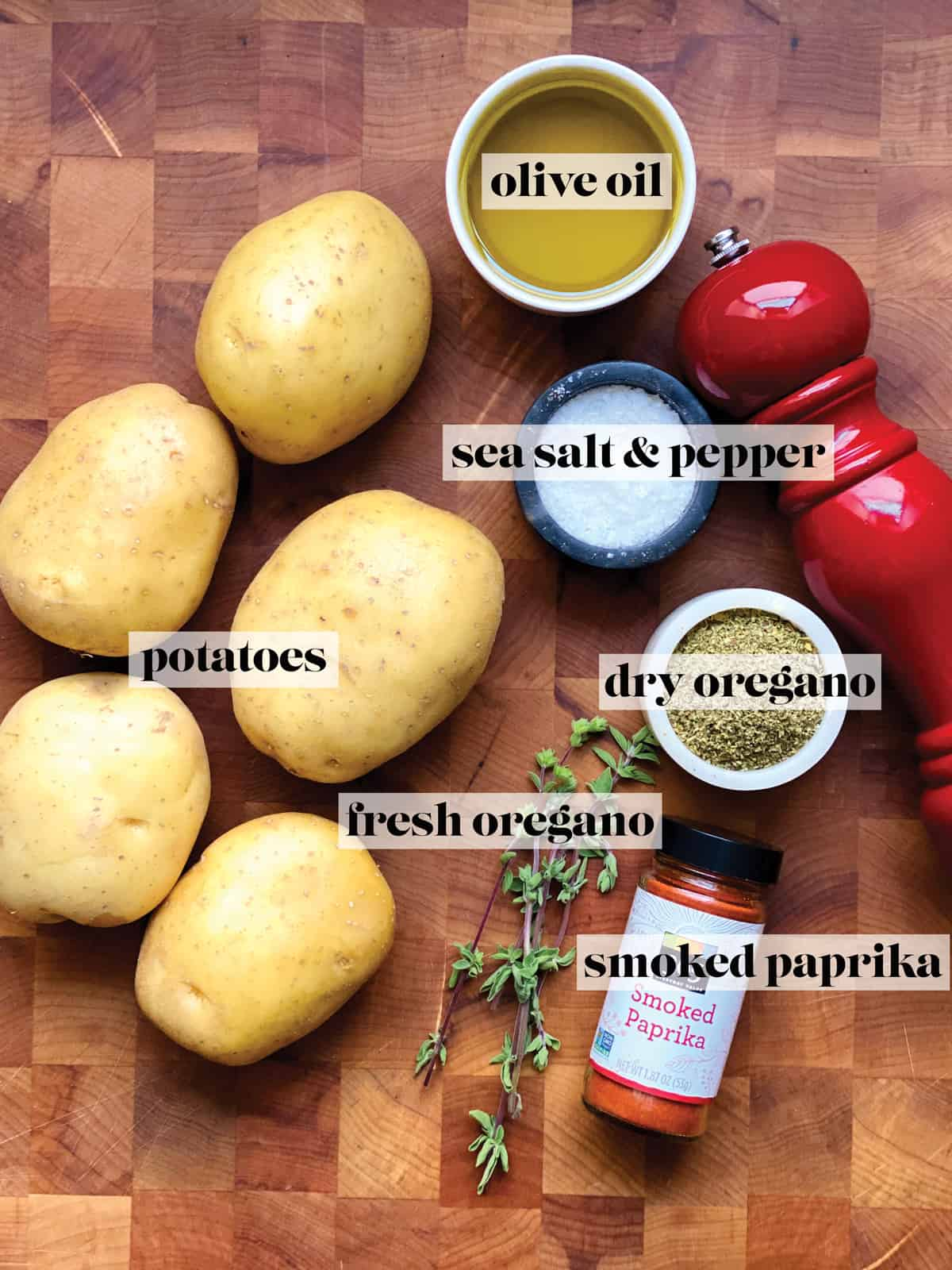Potatoes, small containers with olive oil, salt, oregano, paprika, oregano sprigs and a pepper grinder on a butcher block.