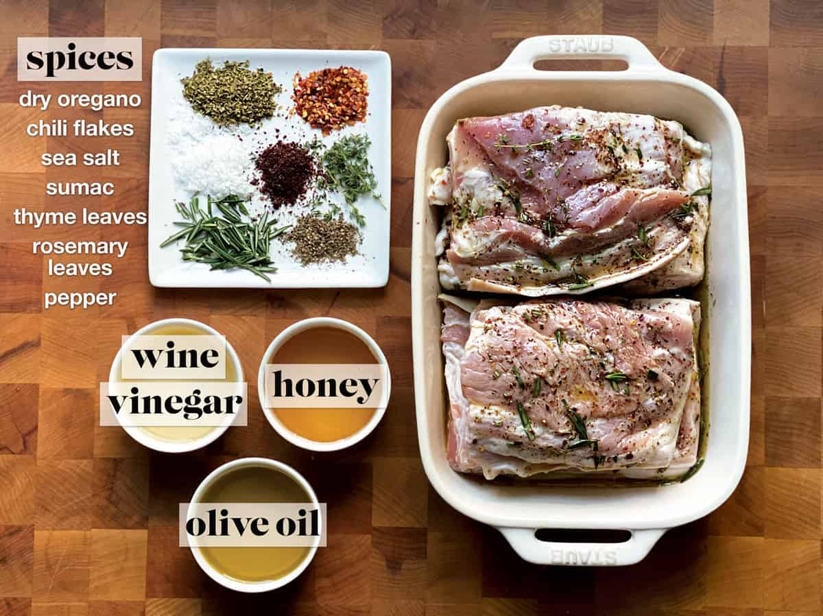Spices on a plate a pan with pork marinating, and three small bowls with vinegar, honey, and olive oil.