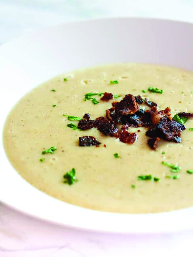 A bowl with roasted parsnip and potato soup with bacon bits on top.