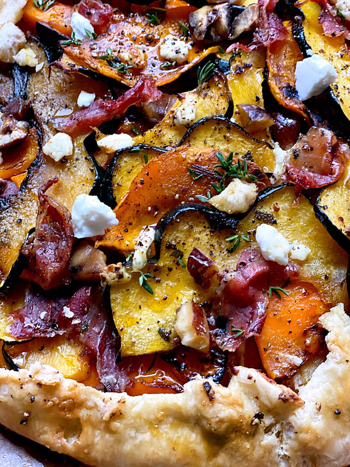 A squash galette with proscuitto and maple syrup on parchment paper.