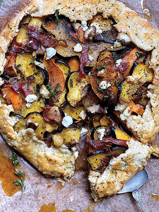 A squash galette with prosciutto and maple syrup on parchment paper.