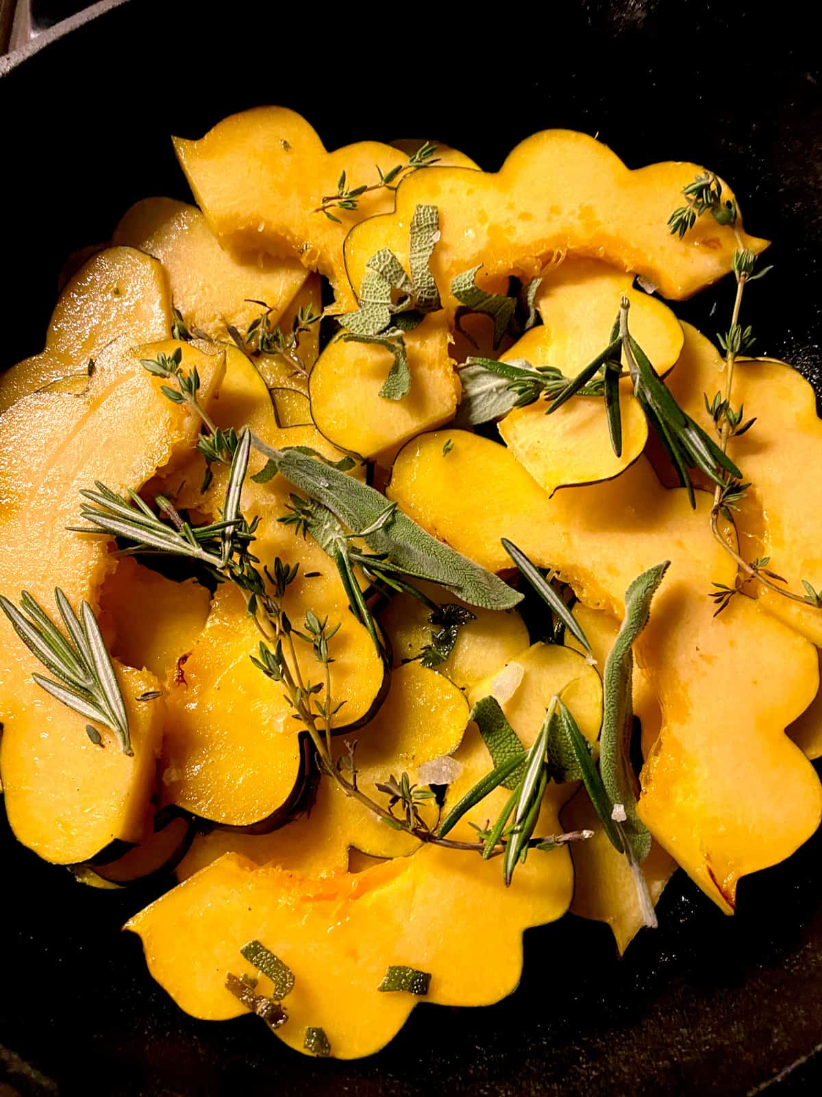 Acorn squash slices with herbs in a skillet.