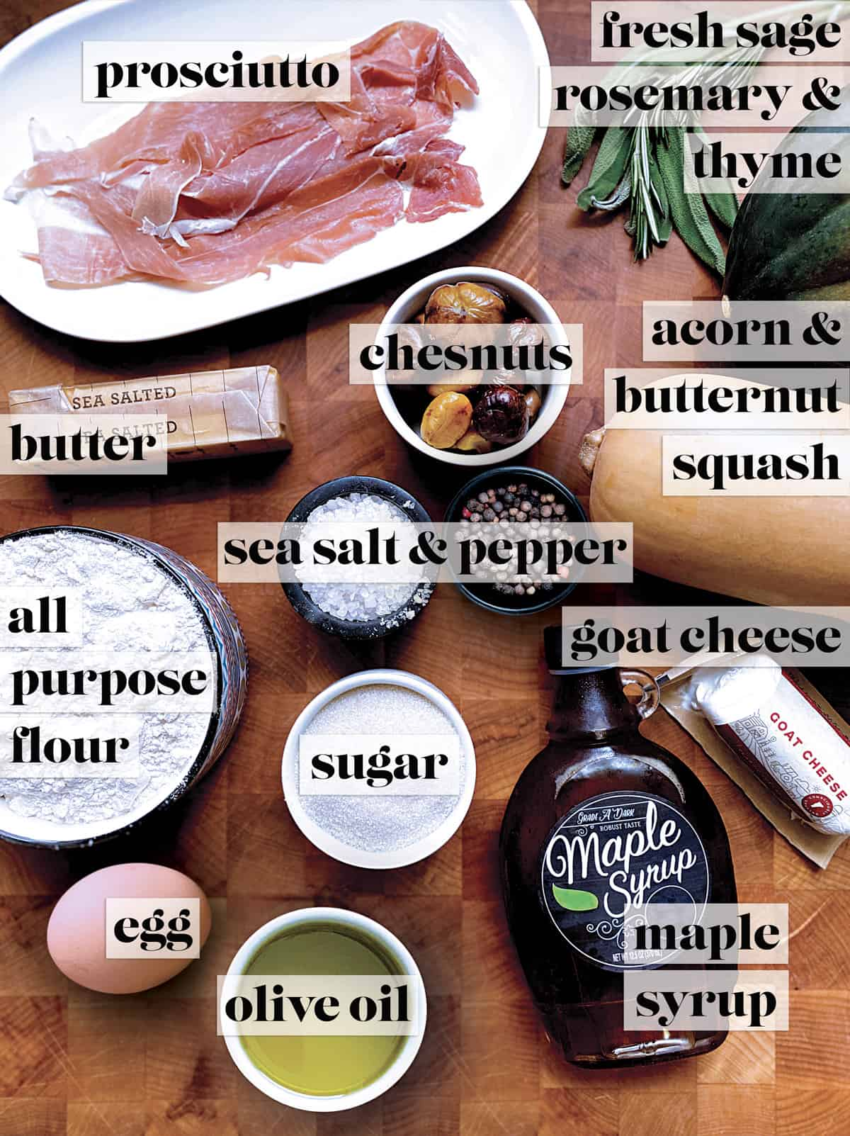 A plate with prosciutto, some herbs, a stick of butter, a bowl with chesnuts, an acorn and a butternut squash, salt and pepper, a bowl with flour, a bowl with sugar, a bottle of maple syrup, a piece of goat cheese, an egg, and a bowl with olive oil on a butcher block