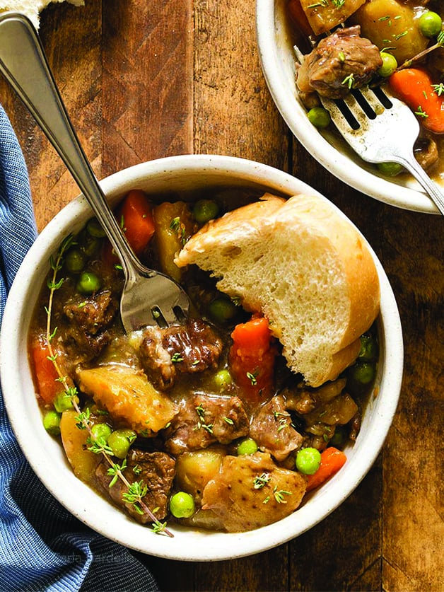 Two mini pots with beef stew with potatoes, carrots, and peas.