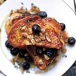 A plate with Tsoureki -greek brioche bread French toast blueberries, walnuts and honey.