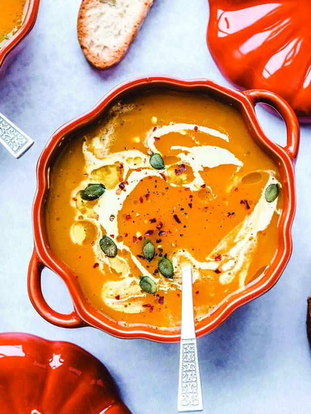 A pumpkin shaped bowl with vegan pumpkin soup.