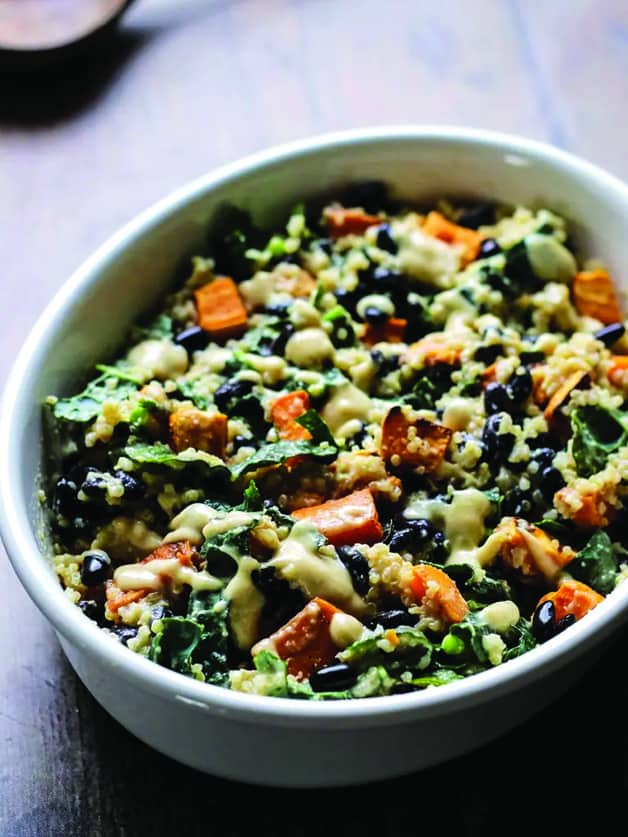 A plate with sweet potato casserole with black beans, kale, quinoa and roasted garlic sauce.